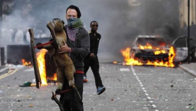 Un joven sujeta un juguete frente a un coche ardiendo, durante los enfrentamientos que se viven en el conflictivo barrio de Hackney, al este de Londres.