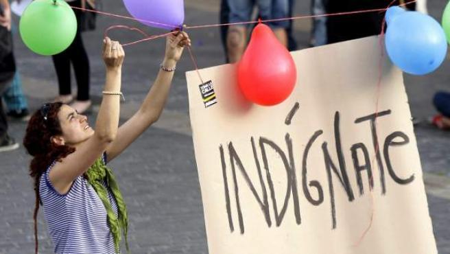 Una joven cuelga una pancarta del movimiento 15-M.