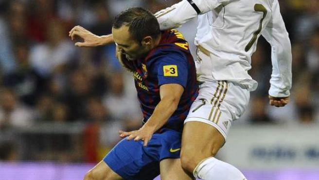 Cristiano Ronaldo e Iniesta pugnan.