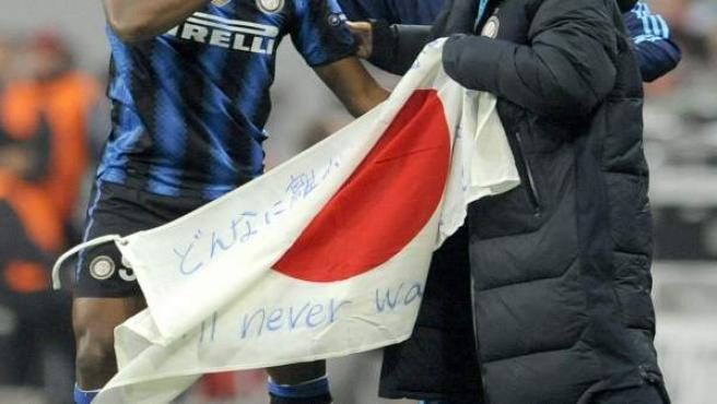 El delantero camerunés del Inter de Milán Samuel Eto'o (i) celebra su gol contra el Bayern Munich con su compañero japonés Yuto Nagatomo (d) y la bandera de Japón.