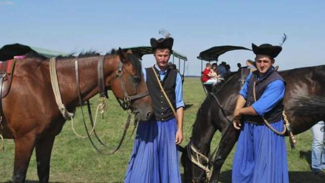 Varios jinetes vestidos con el traje típico de la región húngara.