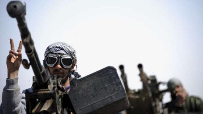 Un soldado rebelde libio hacer la señal de victoria mientras maneja una ametralladora en un punto de control.