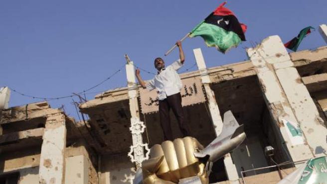 Un rebelde libio ondea su bandera sobre el monumento que recuerda el bombardeo de EE UU en 1986 en Trípoli.