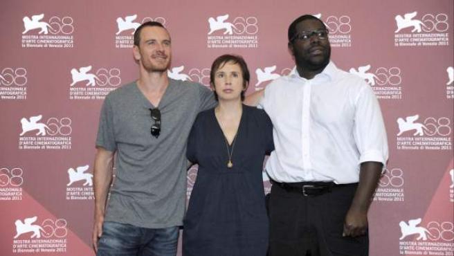 El director Steve McQueen (d), junto al actor Michael Fassbender (i), y la guionista Abi Morgan (c). McQueen ha presentado su última película, 'Shame', protagonizada por Fassbender, en el Festival de Venecia.