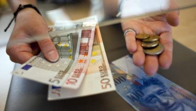 Fotografía de archivo tomada el 8 de junio de 2011 que muestra a una mujer cambiando francos suizos por euros en un mostrador en Kreuzlingen (Suiza).