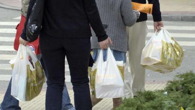 Varias personas usando bolsas de plástico.