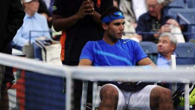 El tenista español Rafael Nadal espera en su silla a que pare de llover en el US Open.