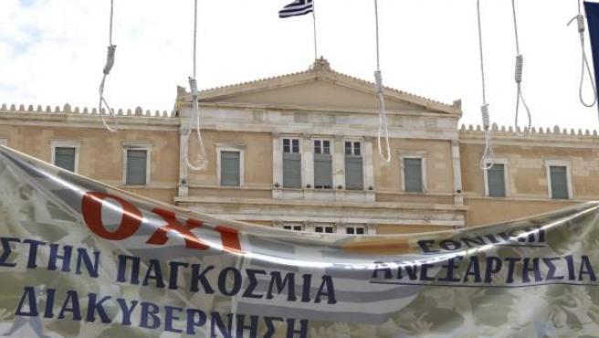 Un hombre coloca una pancarta frente al Parlamento griego, donde ondea la bandera griega en la segunda jornada de protestas dentro de la huelga general contra el nuevo plan de ajuste planteado por el Gobierno.