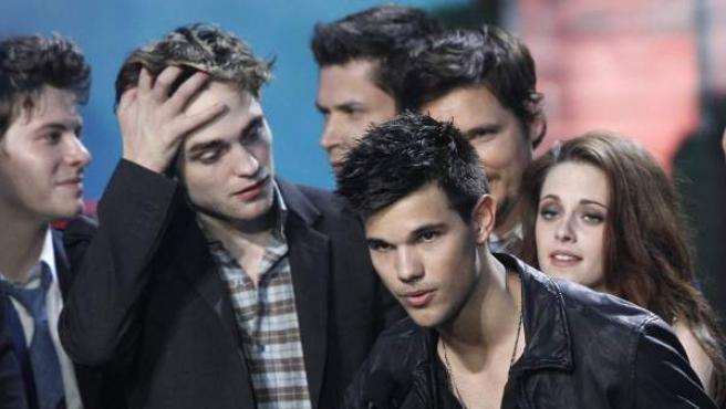 Taylor Lautner acepta en nombre del equipo artístico el premio MTV a la mejor película para 'Eclipse'. Lo contemplan divertidos el resto del reparto, entre ellos Robert Pattinson y Kristen Stewart.