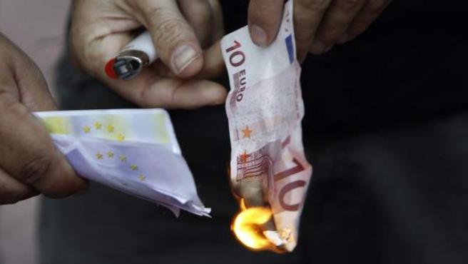 Manifestantes griegos queman billetes de euro ante la sede del Banco de Grecia.