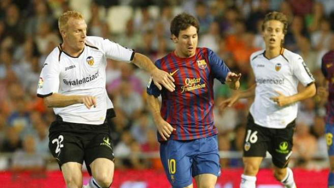 Messi disputa el balón ante el valencianista Mathieu.