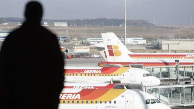 Un hombre observa varios aviones en el aeropuerto de Barajas.