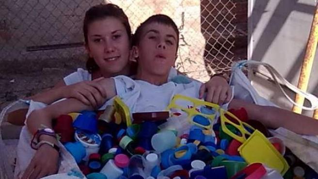 Javier (d), uno de los chicos que padece la Ataxia-telangiectasia, en la imagen junto a su hermana, y rodeado por los tapones que la AEFAT está recogiendo para recaudar dinero, y así que comiencen las investigaciones sobre esta 'enfermedad rara'.