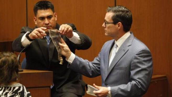El abogado de la defensa, Ed Chernoff, entrega una bolsa de cloruro de sodio al director de logística de Michael Jackson, Alberto Álvarez, durante la tercera jornada del juicio por la muerte del cantante.