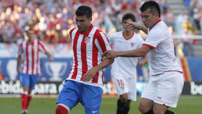 José Antonio Reyes, extremo del Atlético de Madrid, protege el balón ante Gary Medel, del Sevilla.