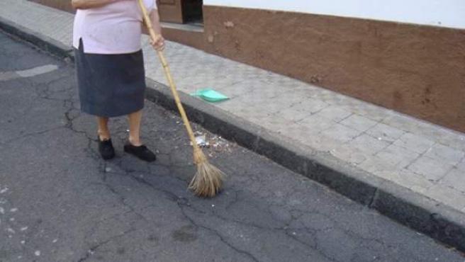 Una mujer barriendo la calle.