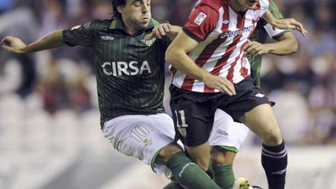 El centrocampista del Real Betis, Beñat Etxebarria (i), intenta robarle la pelota al centrocampista del Athletic de Bilbao, Igor Gabilondo.