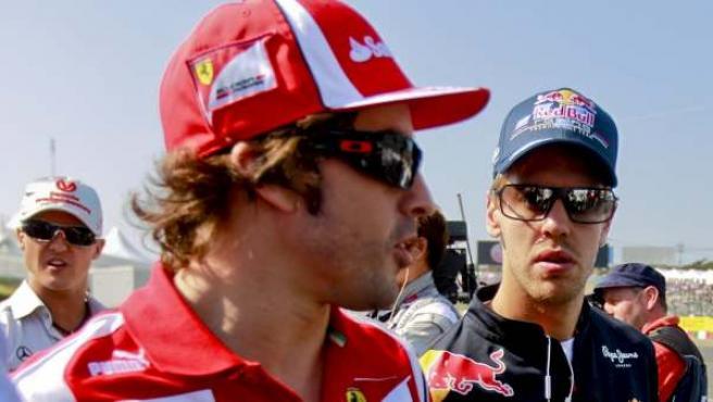 El piloto español Fernando Alonso (izq), de Ferrari, conversa con el alemán Sebastian Vettel, de Red Bull.