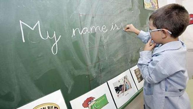 Niño escribe inglés en la pizarra del colegio