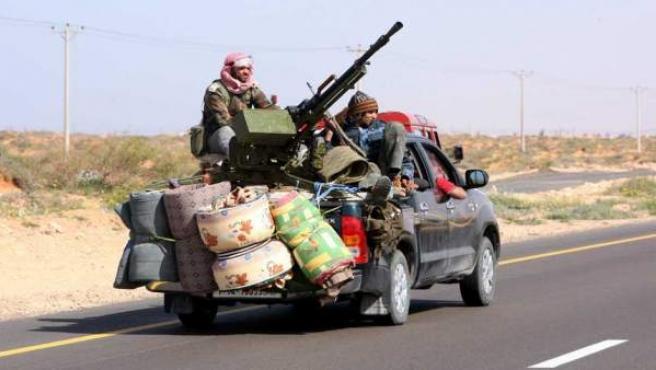 Un grupo de rebeldes libios circula en una furgoneta armada con una ametralladora, por la carretera entre Bin Jwad y Sirte, Libia.