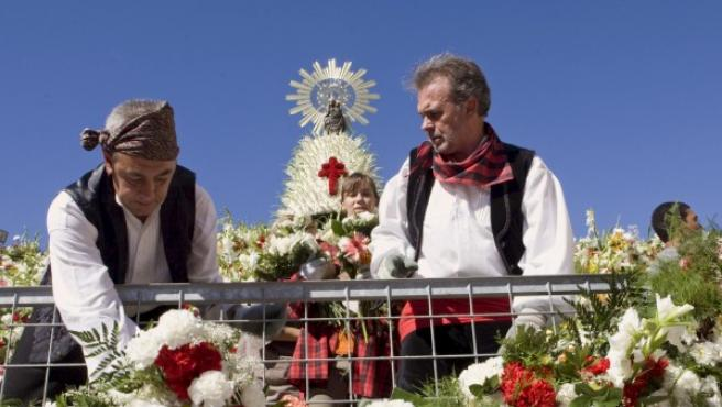 Varias personas ataviadas con el traje regional aragonés utilizan un ramo de flores para tejer el manto floral de la Virgen del Pilar.
