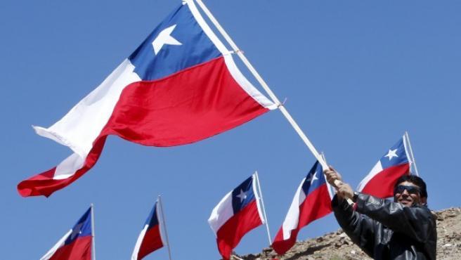 El minero Claudio Yañez ondea una bandera de Chile durante el homenaje en Copiapó para conmemorar el primer año del rescate de los 33 mineros.
