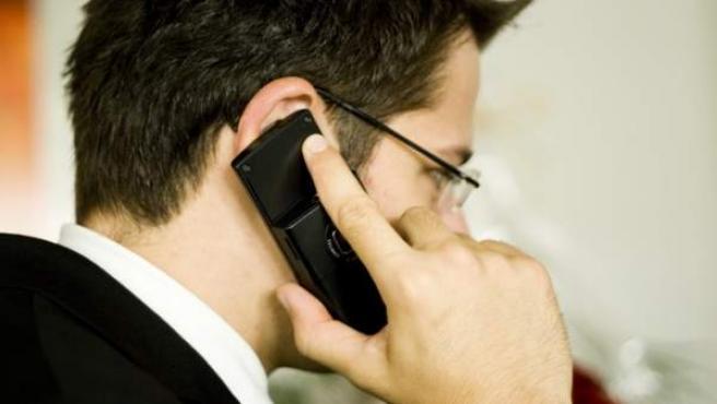 Un hombre habla por teléfono móvil.