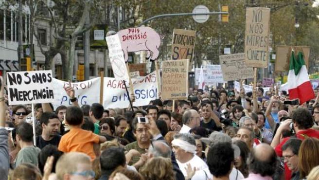 """Plaza de Cataluña es el epicentro de la marcha del 15-O en Barcelona, en donde algunos manifestantes llevan pancartas con la frase """"Puig dimisión""""."""