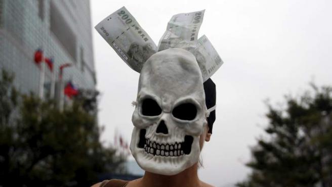 Un activista lleva una máscara con nuevos dólares de Taiwán mientras participa en la protesta global del 15-O en Taipei.