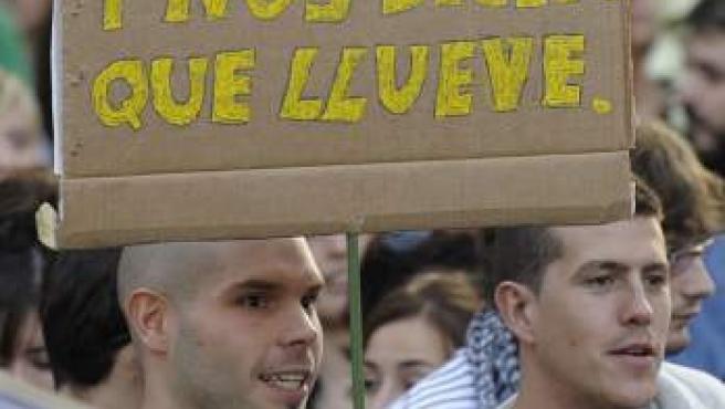 Un joven muestra una pancarta durante la manifestación de miles de 'indignados' por las calles de Valladolid.