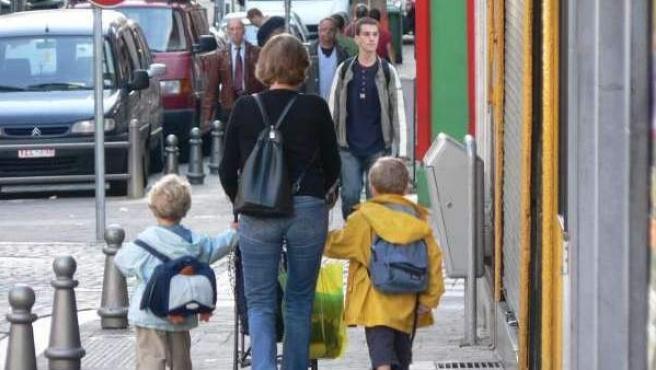 Una madre pasea junto a sus hijos.