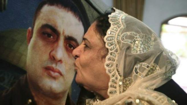 Una palestina besa la foto de su hijo, Raafat Aroki, encarcelado en una prisión de Israel.