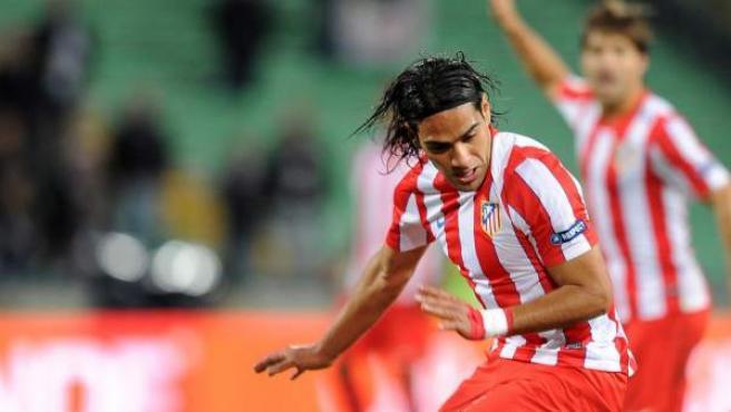 El jugador del Atlético de Madrid Falcao lucha por la bola con el jugador del Udinese Thierry Doubai.