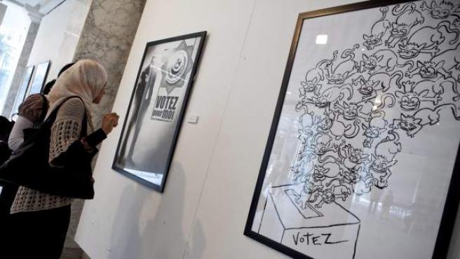 Unas mujeres observan unos carteles que animan a la participación en las elecciones en una galería de arte en Túnez.