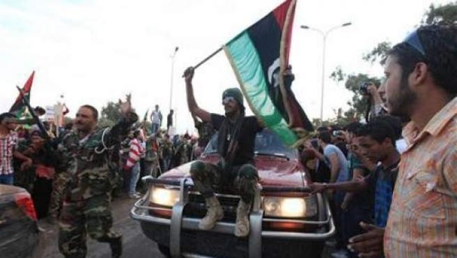 """Ciudadanos libios dejan paso, en medio de un ambiente festivo, a un vehículo en el que los rebeldes que porta una bandera de """"la nueva Libia""""."""
