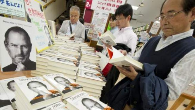 Varias personas observan la nueva biografía del fallecido fundador de Apple, Steve Jobs, escrita por el estadounidense Walter Isaacson, que llegó a las librerias niponas, el lunes 24 de octubre, en Tokio, Japón.