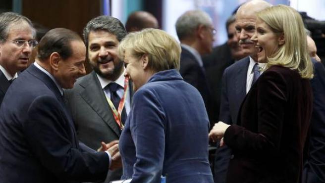 El primer ministro italiano, Silvio Berlusconi, saluda a la canciller alemana, Angela Merkel.