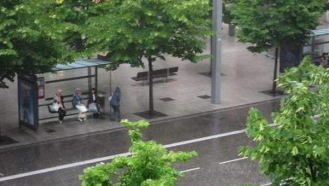 Varias personas se resguardan de la lluvia bajo una marquesina.