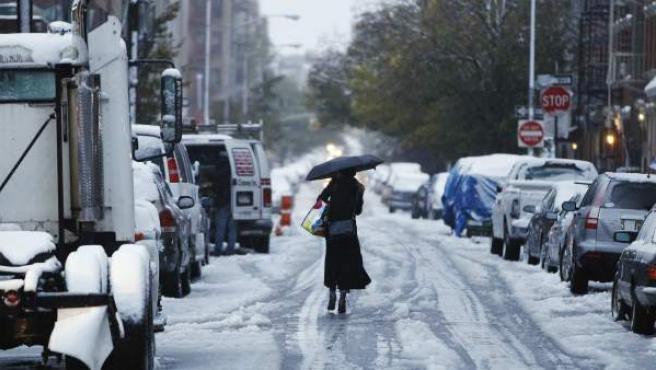 Una mujer camina en una calle de Nueva York blanca por la tormenta de nieve.