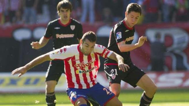 El jugador del Sporting de Gijón David Barral (c) se lleva el balón ante la presión de Ander Herrera (d), del Athletic de Bilbao.