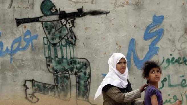 Dos chicas palestinas juegan ante pintadas en un muro del en el campamento para refugiados de Rafah, en la Franja de Gaza.