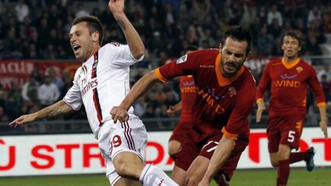 Antonio Cassano, delantero del Milan, recibe una falta de Marco Cassetti, defensa de la Roma.