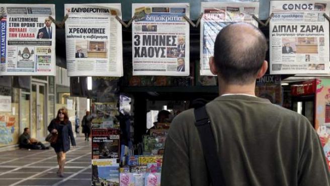 Un ciudadano griego observa las portadas de los diarios en un quiosco en el centro de Atenas.