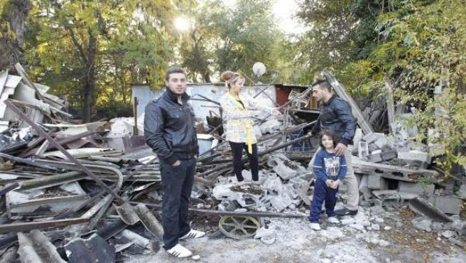 Francisco y su familia sobre los restos de su chabola, derribada este martes.