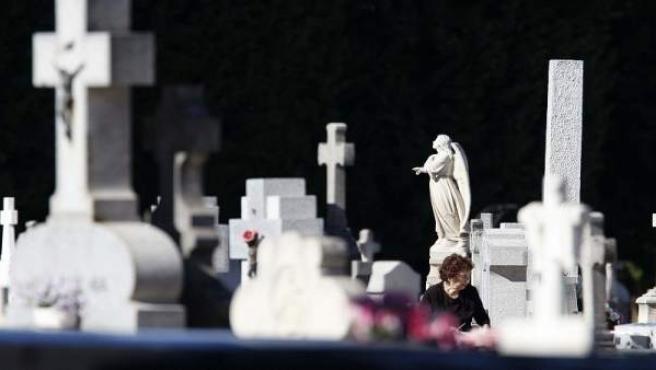Una mujer visita a sus difuntos en el cementerio de La Almudena de Madrid.