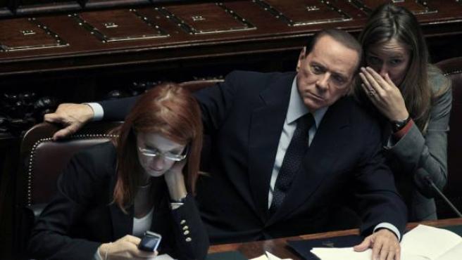 El primer ministro italiano, Silvio Berlusconi, escucha a su ministra Stefania Prestigiacomo.