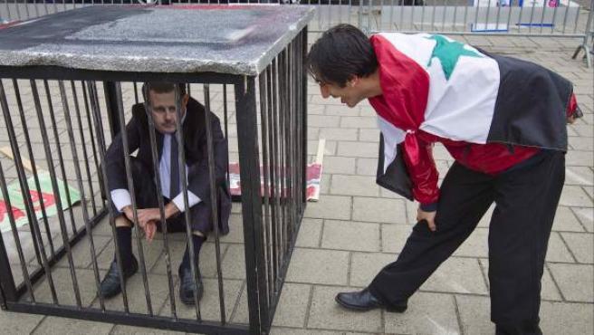 Un hombre con una bandera siria contempla a un compatriota enjaulado que lleva la máscara del presidente Bashar al-Assad, durante una protesta contra el régimen sirio, frente al Tribunal Penal Internacional de La Haya (Holanda).