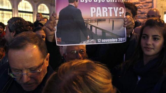 """Un hombre sostiene una pancarta que reza """"Adiós, Silvio"""" (""""Bye bye, Silvio""""), junto al palacio Chigi de Roma."""