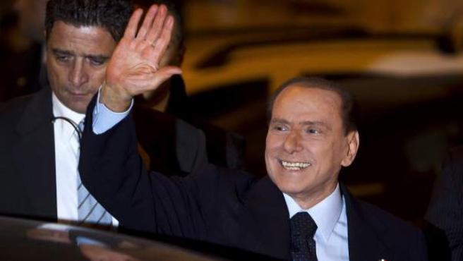 El exprimer ministro italiano, Silvio Berlusconi, saluda a sus simpatizantes a su llegada al Palacio Grazioli de Roma.