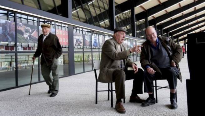 Dos personas mayores charlan mientras otra camina por detrás.